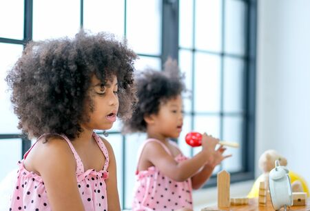Two young African girls play toys and act as sing a song together with main focus on front girl who look boring with activity but the back girl look enjoy.