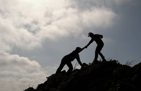 Silhouette image of one friend try to pull his other friend over the cliff of mountain and they climb and help each other during day time of travel.