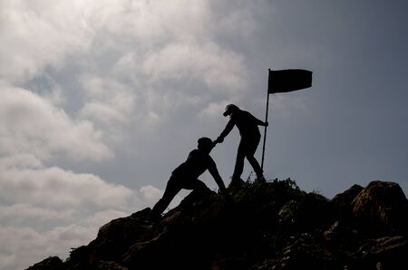 Silhouette image of one friend with flag try to pull his other friend over the cliff of mountain and they climb and help each other with concept teamwork for successful. Stock Photo