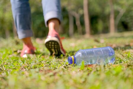 The bottle with water spray is leaved from someone on grass in the garden or part as garbage with concept of damage the environment.