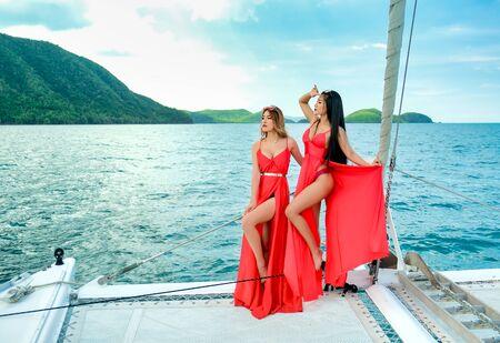Zwei hübsche asiatische Frauen mit rotem Kleid stehen während der Bootsfahrt tagsüber auf dem Bug der Yacht.
