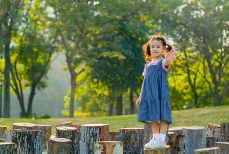 Young asian little girl stand on timber and also wave her hand with morning light in the garden.