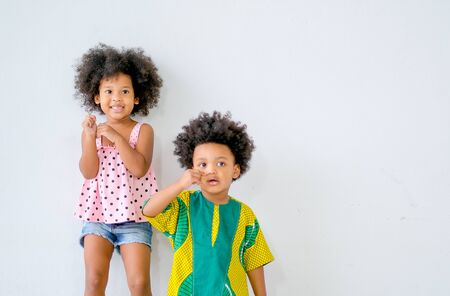 Portrait of young african girl stand behind the boy with white background and show different actions. Banque d'images - 137188462