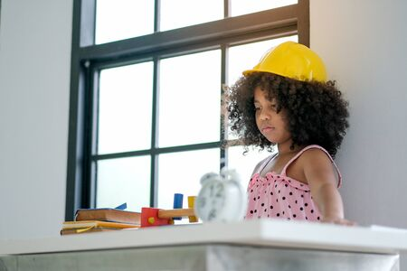 Portrait of young African girl play as engineer by wearing yellow hat in the living room with some decorations. Banque d'images - 137188556
