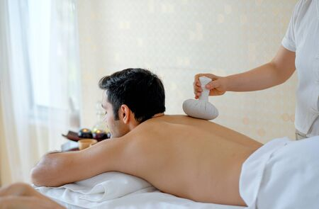 Handsome man enjoying with massage by herbal ball on his back in spa room with day light. Фото со стока