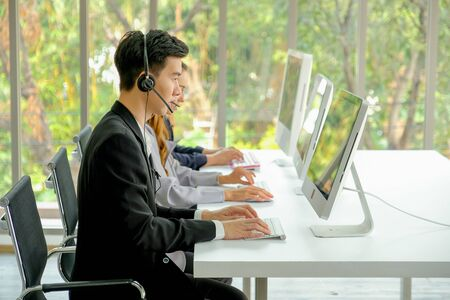 Young man with suit work as operator of the company with different action such as touch headphone or typing.