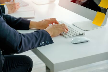 Hands of business man types some data or information to computer during working.