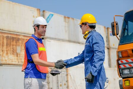 Technician and engineer shake hand in cargo container area with concept collaborate working.