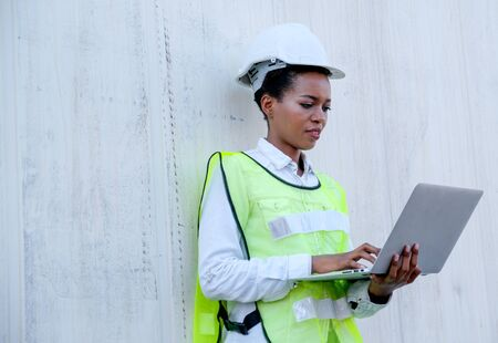 Portrait of African technician worker woman lean on cargo container wall and also hold laptop for working.