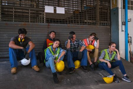 Group of technician or workers sit in front of the door of factory and end of work and they look sad. 写真素材