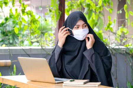 Muslim girl is wearing face mask during work with laptop and she still work at home during Covid-19 pandemic in many area.