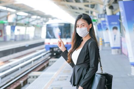 Beautiful business woman with hygiene mask stand in front of sky train wait for going to work during Covid-19 pandemic in the city.