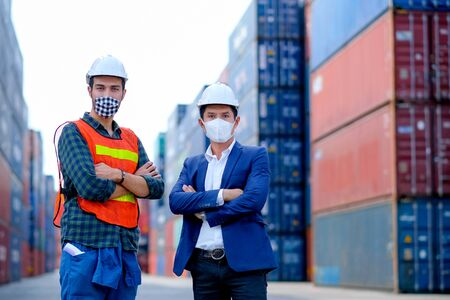 Technician or engineer workers stand in front of shipping container with one hold infrared thermometer and manager also wear face mask in the procedure to prevent virus infection in workplace area. Foto de archivo