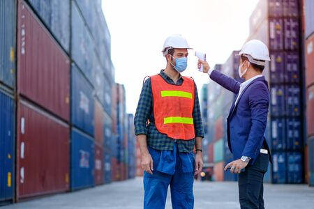 Manager or engineer worker use infrared thermometer measure temperature of other staff in shipping container workplace area Concept of prevent infection during covid pandemic around the world.