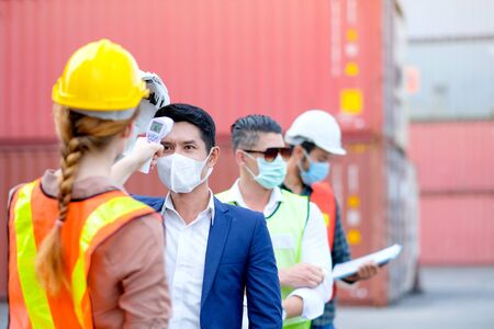 Technician or engineer worker use infrared thermometer measure temperature of other staff in shipping container workplace area and they stay in line during covid pandemic in around the world.
