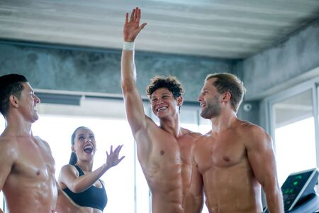 Main focus in sport man raise one's hand and smile show happy emotion with friends in gym with day light. Concept of good health to get better body health prevent disease include occur from virus.