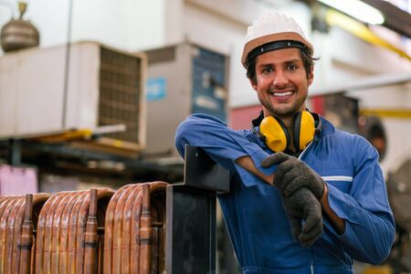 Factory worker man stand near copper tube or pipe and smiling in workplace look happy. Concept of good management system for industrial business.