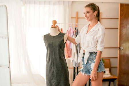 Beautiful woman stay in bedroom and look to mirror with her dress and express proud of her design work. Concept of new normal lifestyle for selling online and work at home.