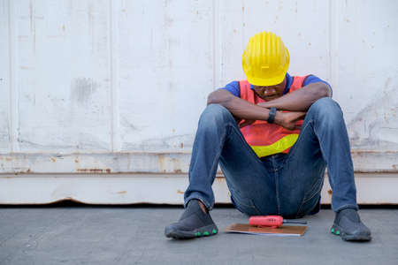 American African engineer or factory worker man sit close to cargo container and he look tire and also sleepy or lost job. Concept of good system and manager support for better industrial business.