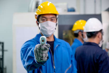 Infrared thermometer is holding by factory worker man and use for measure and screening temperature of other co-workers in industrial workplace.