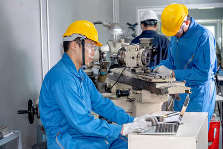 Factory worker man with blue uniform and yellow hard hat work with laptop in front of other co-worker are working with the machine in workplace area. They look concentrate with their industrial work.