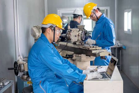 Factory worker wearing yellow hard hat work by using laptop to analysis his work and other workers work with the machine. They action with concentrate to their work in workplace area.