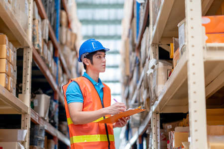 Warehouse man or factory worker with blue hard hat and uniform stand between shelves and check package in workplace. Concept of good management and happiness of staff during work industrial business.