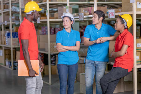 Group of warehouse or factory workers stay and talk together during breaking from work and they look relax in workplace area. Concept of support system for staff in delivery industrial business.