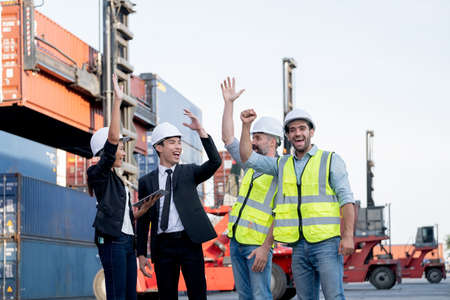 Cargo container workers or group of employee express happy emotion and action look lite celebrate with successful of work in workplace area with crane and shipping container stack as background.