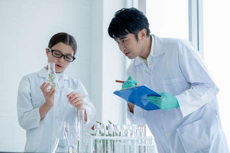 Young Caucasian scientist child girl hold flask with plant tissue and explain to her Asian teacher with record some data during do experiment in laboratory or classroom.