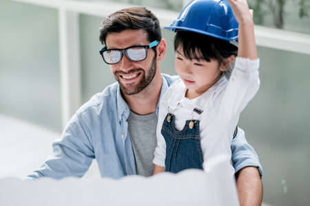 Main focus on Caucasian man work with happy emotion to stay with his daughter during work at home new normal lifestyle.