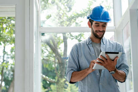 Caucasian engineer man with blue hardhat use tablet in office with glass window and he look happy with work. Stock fotó