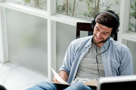 Soft blurred of Caucasian man read book and listen music by headphone with relax and happy expression in room with day light. Stock fotó