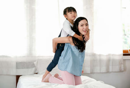 Asian mother and little girl have fun by girl hug on back of mother and stay on bed with happy and relax emotion. Stock fotó