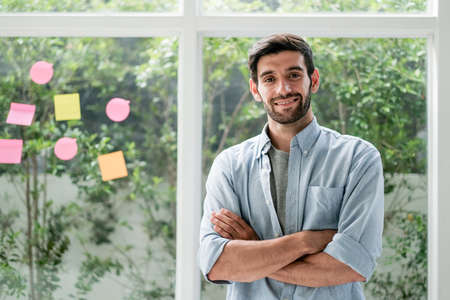 Business Caucasian man stand with arm crossed and confidence action with smiling look at camera in office with grass window and some note as background. Stock fotó