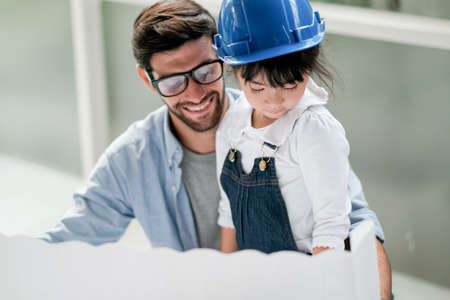 Main focus on little girl enjoy with her father during work at home and look to paper. Stock fotó