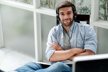 Caucasian man listen music by headphone and sit in room with glass windows with relax and happy expression also look at camera in room with day light. Stock fotó