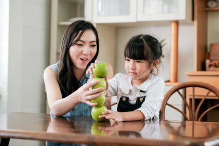 Asian mother and little girl enjoy together to set stack of green apple on table in the kitchen with happiness emotion.