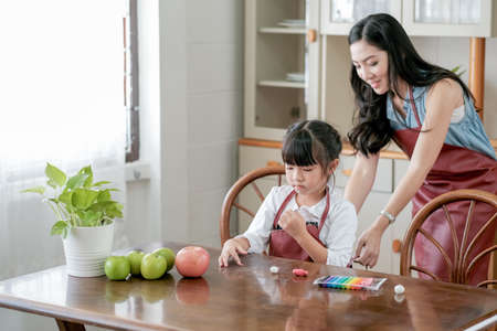 Little girl enjoy to play with play dough in kitchen on the table while her mother try to dress her with apron. Asian family with happiness concept.