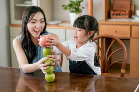 Asian mother excite and happy when her little girl put red apple over stack of green apple on table in the kitchen. Stock fotó