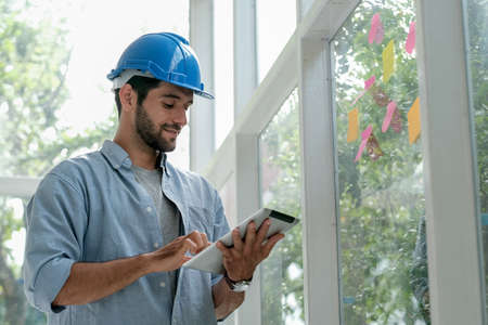 Caucasian engineer work in office with glass windows and use tablet to manage system also contact with other co-worker.