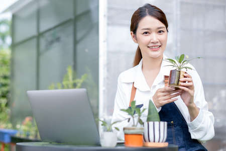 Beautiful Asian girl hold pot of plant and present to camera sit with laptop on table in front green garden of her house. Sustainable with grow cactus and other plant concept.