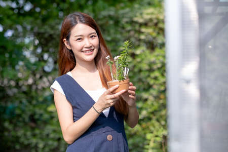 Beautiful Asian girl hold pot of plant and stand near green house with day light. Sustainable with grow cactus and other plant concept.
