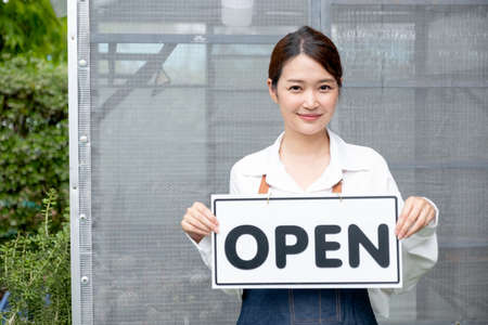 Beautiful Asian woman present banner with word open in front of green house and happy emotion relate with re-open the business with sustainable activity.