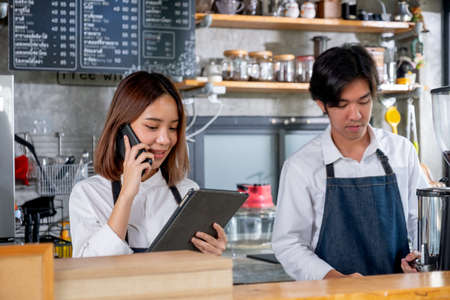 Barista girl or coffee maker receive phone call and record order and stand beside of co-worker man in coffee shop. Concept of happy working with small business and sustainable together.