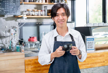 Barista man of coffee maker hold a cup and stand in front of counter in coffee shop with looking at camera and smile. Concept of happy working with small business and sustainable.