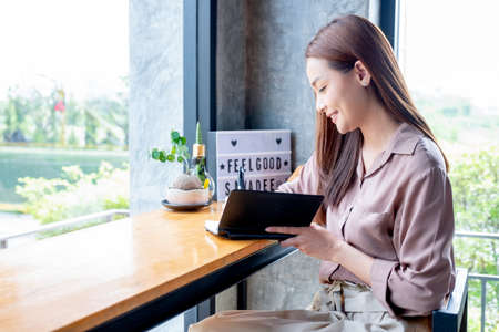 Beautiful Asian woman write some data on notebook and sit in corner of coffee shop with day light. She is smiling with happy emotion and think about her small business.