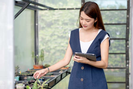 Beautiful Asian girl hold tablet to check quality and physical of plant product in her green garden of her house. Sustainable with business work involve with plant of flora concept. Stock fotó