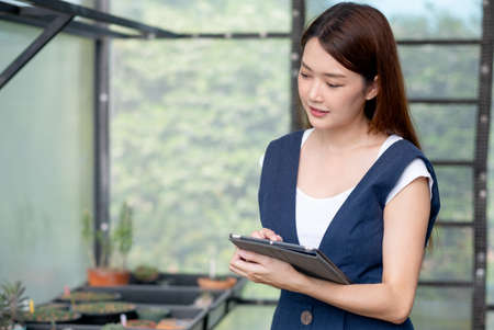 Close up portrait beautiful Asian woman hold tablet to check quality and physical of plant product in her green house. Sustainable with business work involve with plant of flora concept.