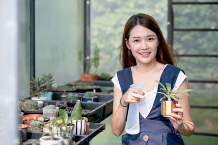 Beautiful Asian girl hold foggy bottle for spraying water to plant in small pot and sit in green garden in her house. Sustainable with grow cactus and other plant concept.